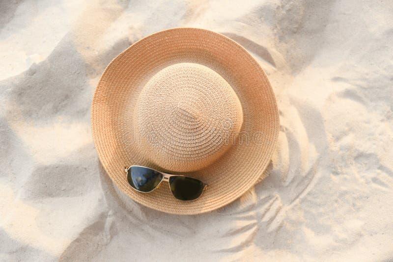 verão do chapéu - fasion do chapéu de palha e acessórios dos óculos de sol na opinião superior do fundo do mar do Sandy Beach fotografia de stock