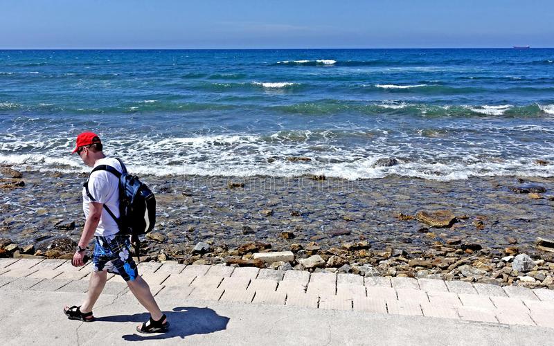 verão em Italia, um homem com um ódio vermelho anda na frente do mar foto de stock royalty free