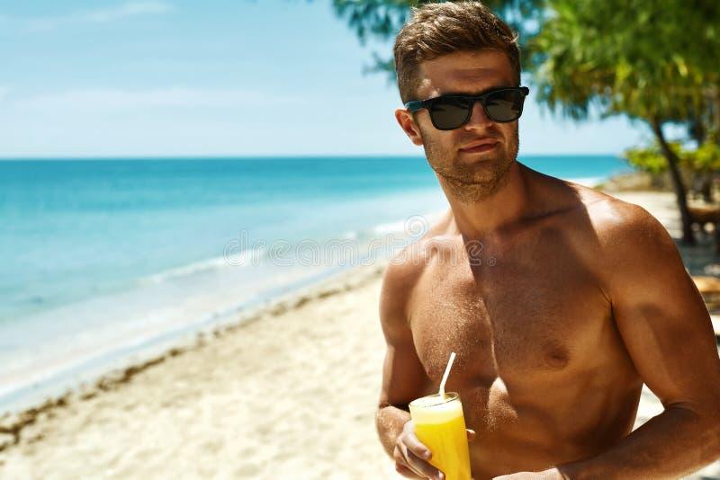 verão Homem muscular atlético que bebe Juice Cocktail On Beach fotos de stock