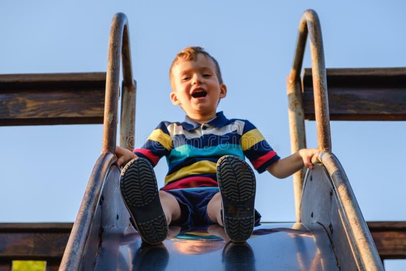 verão, infância, amizade e conceito dos povos - o rapaz pequeno feliz no campo de jogos das crianças deslizou do monte fotos de stock royalty free