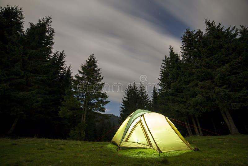 verão que acampa na noite Barraca iluminada do turista no esclarecimento verde no fundo distante da montanha fotos de stock royalty free