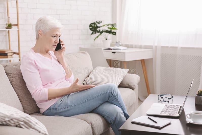 Verärgerte ältere Frau, die über Probleme mit Laptop sich beschwert lizenzfreies stockfoto