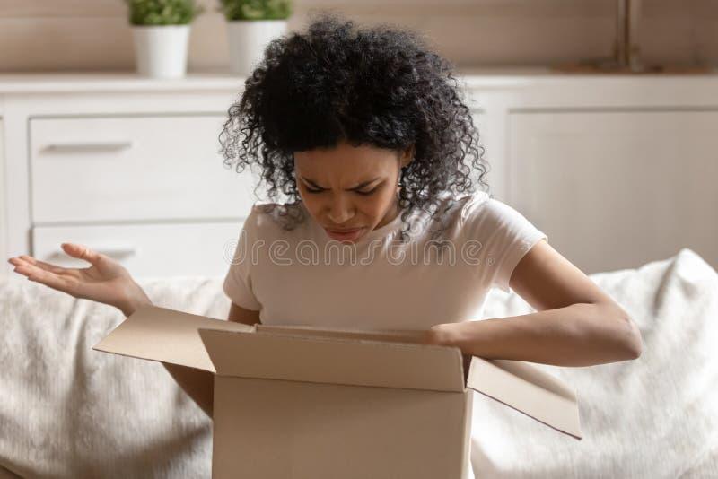 Verärgerte afrikanische Frau packen Kartonkasten glaubt gereizt aus lizenzfreies stockfoto