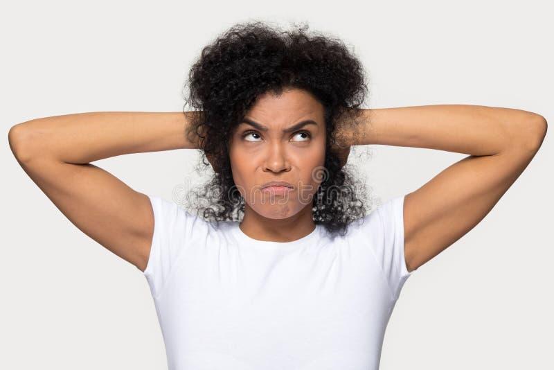 Ver?rgerte afrikanische Frau schloss ihre Ohren mit Handatelieraufnahme stockbilder