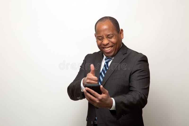 Verärgerte Afroamerikaner-Geschäftsmann-Gespräche am Telefon auf hellem Gray Background stockbilder