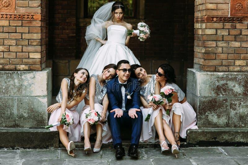 Verärgerte Braut und Bräutigam mit den Brautjungfern stockfotos