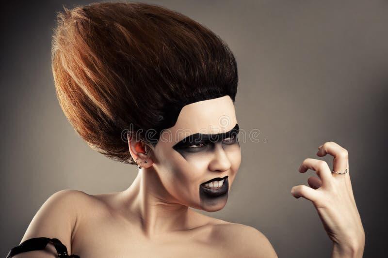 Verärgerte Brunettefrau mit dunkler Make-up und Stofffrisur stockbilder