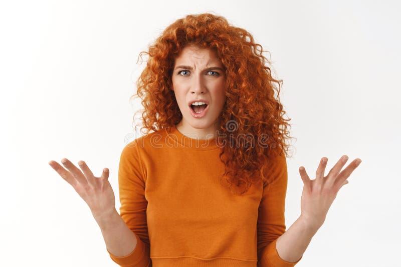 Verärgerte empörte attraktive, stilvolle Rothaarigefrau, die Hände im Schrecken, Beschwerdestarren frustriert und wütend anhebt lizenzfreie stockfotos