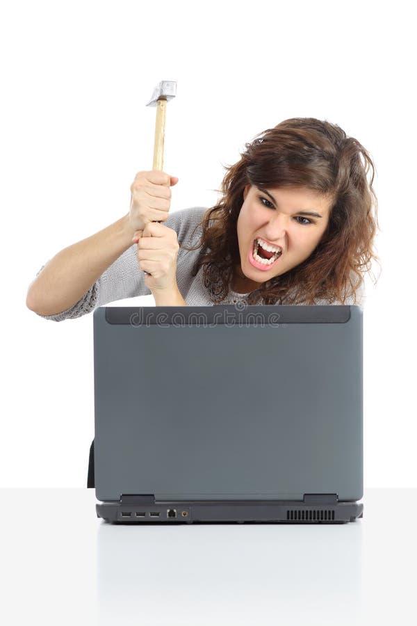 Verärgerte Frau bereit, einen Computer mit einem Hammer zu zerstören stockbilder
