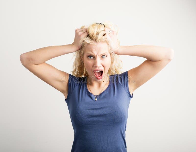 Verärgerte Frau, die ihr Haar herauszieht stockbilder