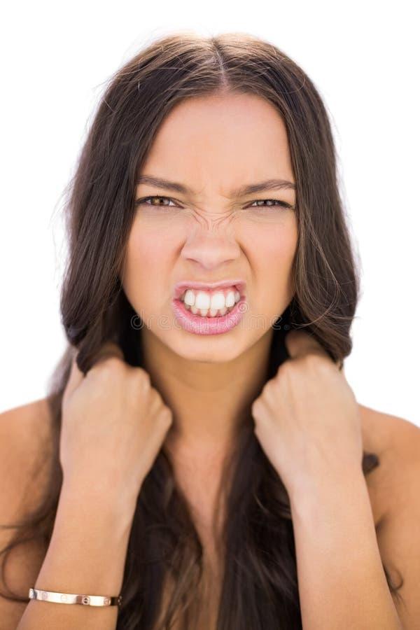 Verärgerte Frau, die ihr Haar zieht stockfotos