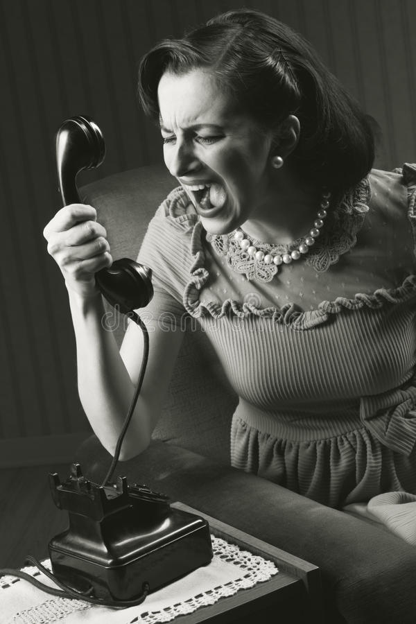 Verärgerte Frau, die am Retro Telefon schreit stockbilder