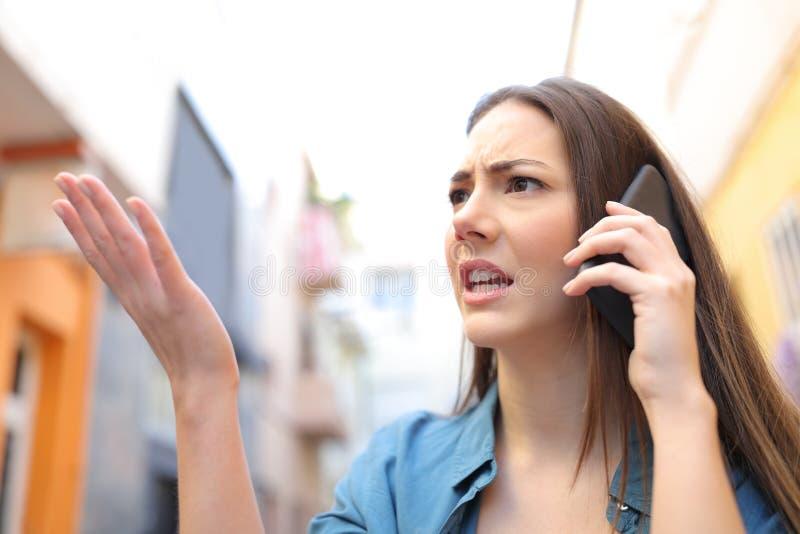 Verärgerte Frau, die am Telefon sich beschwert in der Straße spricht stockfoto