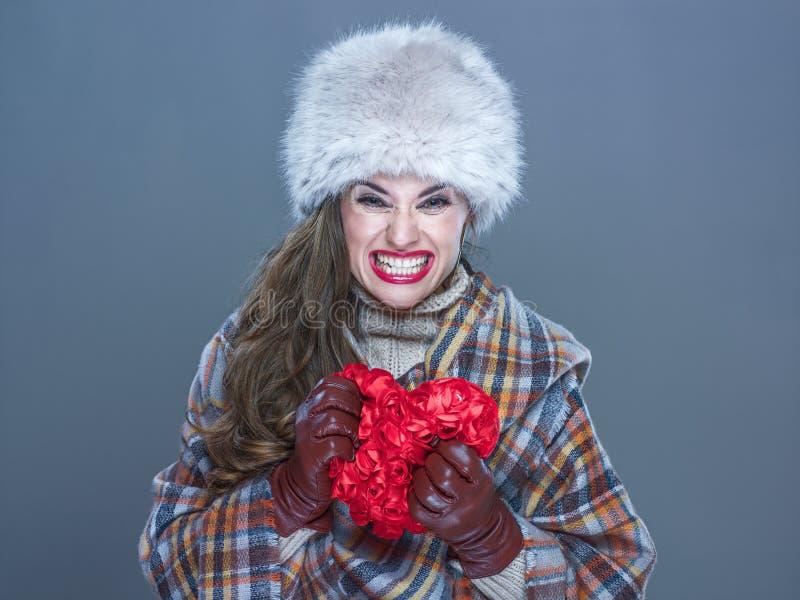 Verärgerte Frau lokalisiert auf dem kalten blauen Hintergrund, der rotes Herz zerquetscht lizenzfreies stockbild