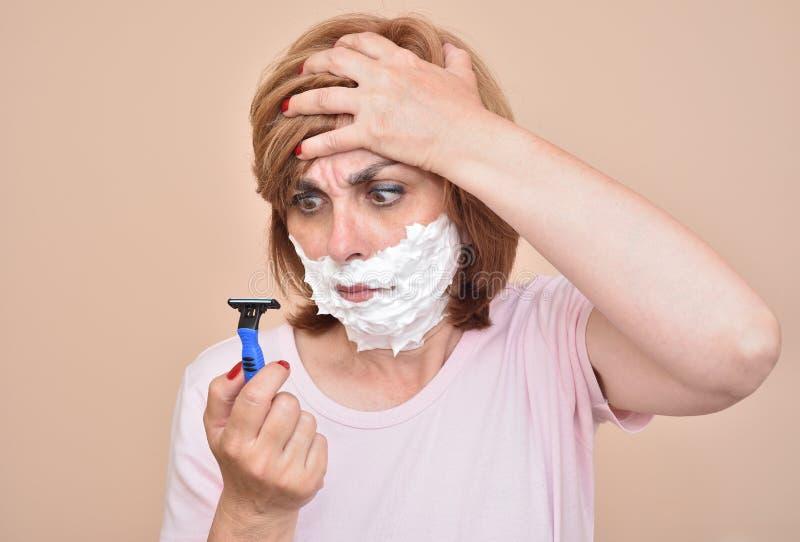 Verärgerte Frau mit dem Rasieren des Schaums auf ihrem Gesicht, das ein Rasiermesser hält und betrachtet stockbilder