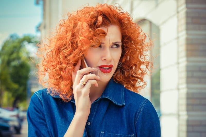 Verärgerte frustrierte, rote Frau des gelockten Haares, die draußen auf Handystellung spricht stockfotos