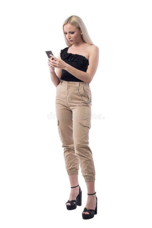 Verärgerte frustrierte stilvolle Blondinelesung und mit Handy stockfoto