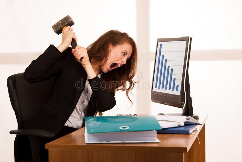 Verärgerte Geschäftsfrau, die Raserei an ihrem Schreibtisch im Büro ausdrückt lizenzfreies stockbild