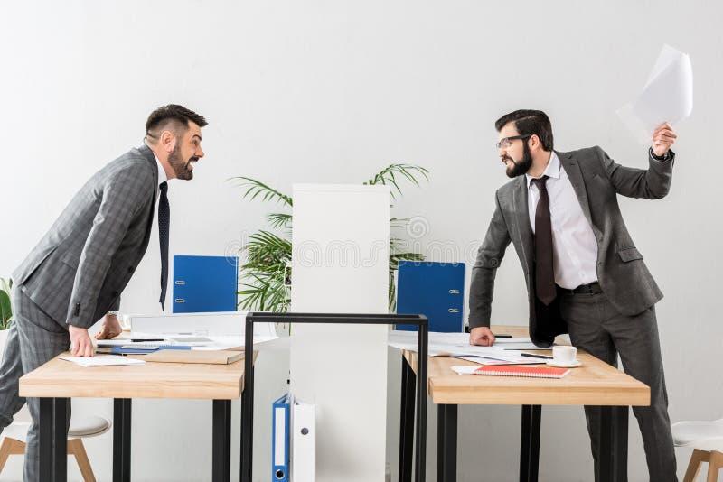 verärgerte Geschäftsmänner, die über Fach streiten stockbilder