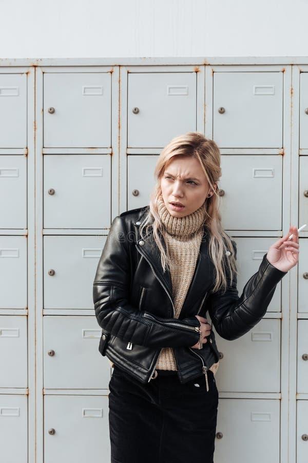 Verärgerte junge blonde Dame, die nahe Safes steht lizenzfreies stockbild