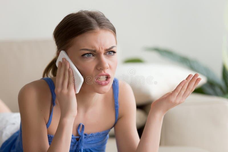 Verärgerte junge Frau, die am Handy zu Hause sprechen argumentiert lizenzfreie stockfotos