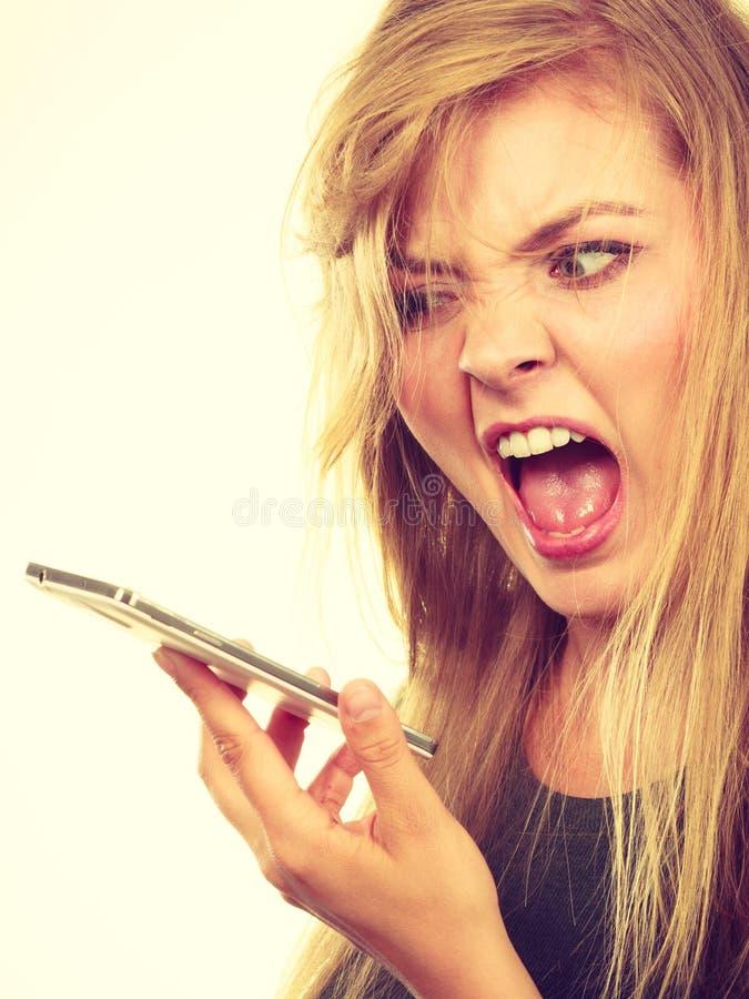 Verärgerte junge Frau, die am Telefon spricht stockbild