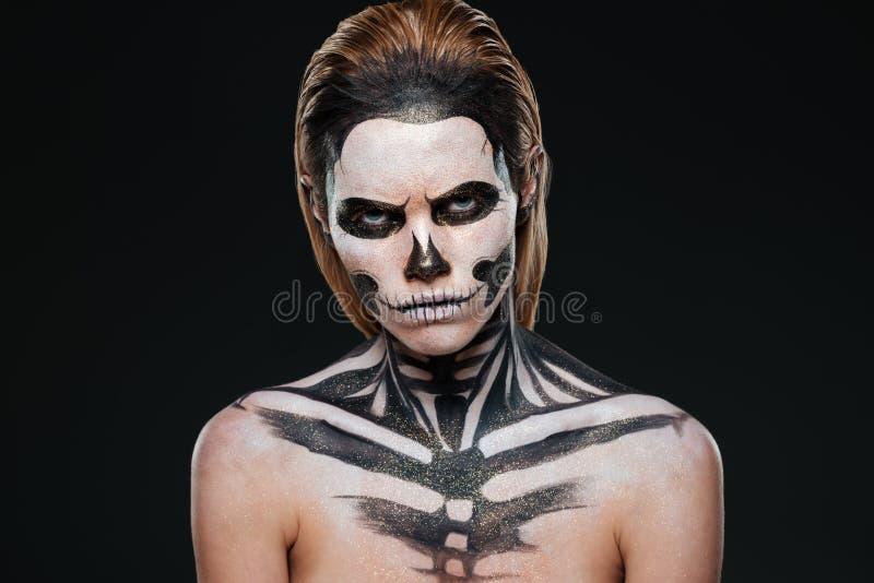 Verärgerte junge Frau mit gotischem Halloween-Make-up stockfoto