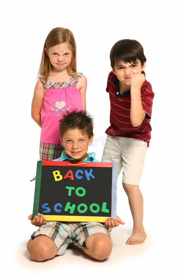 Verärgerte Jungen und Mädchen mit zurück zu Schule-Zeichen lizenzfreie stockfotografie
