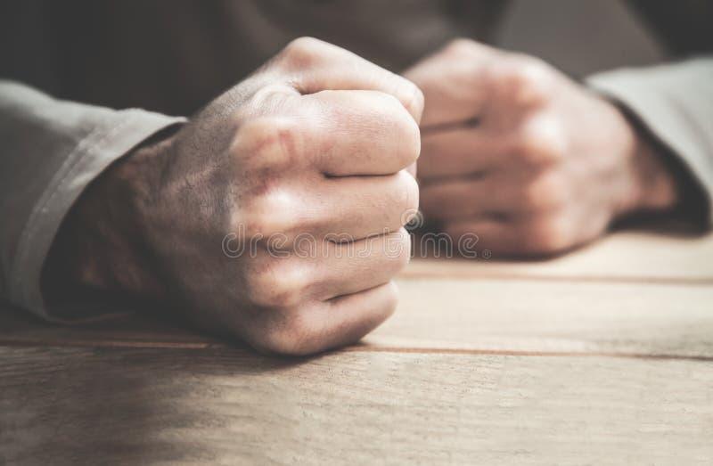 Verärgerte Mannfäuste in der Tabelle stockfoto