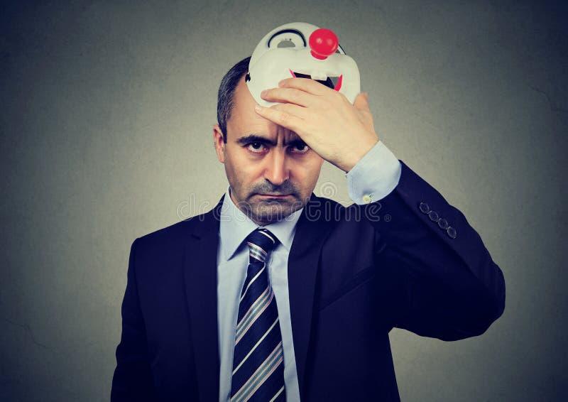 Verärgerte Mitte alterte den Geschäftsmann, der glückliche Clownmaske entfernt stockfotografie