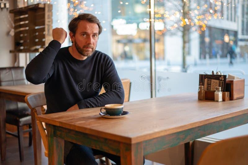 Verärgerte Mitte alterte den kaukasischen Mann, der am Tisch in der Kaffeestube sitzt stockbilder