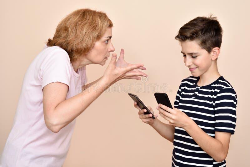 Verärgerte Mutter, die ihren lächelnden Sohn mit zwei Smartphones schilt stockfotografie