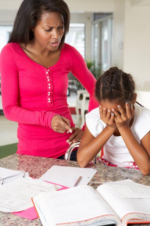 Verärgerte Mutter, die weg von der Tochter über Hausarbeit sagt lizenzfreies stockbild