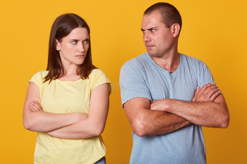 Verärgerte Paarstellung nahe einander, schauend mit Ärger und haben Streit und halten in der Ruhe und haben verschiedene Ansichte stockfoto
