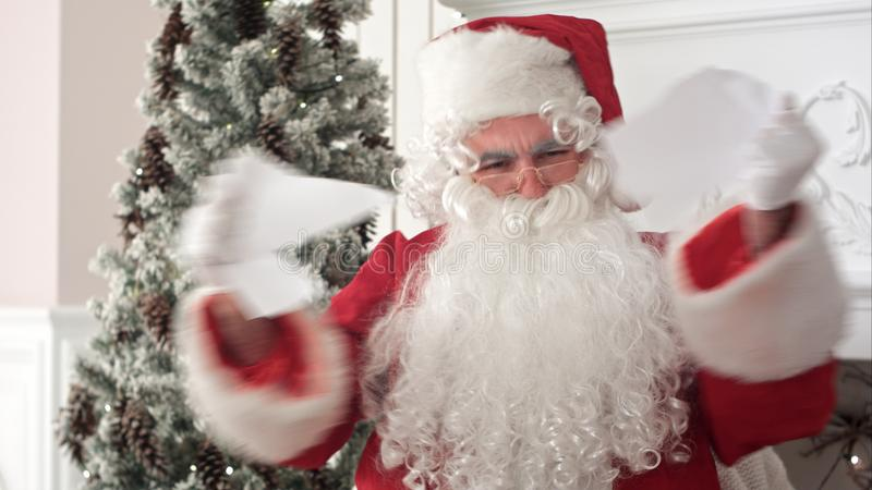 Verärgerte Santa Claus, die einen Brief liest und auseinander ihn zerreißt lizenzfreie stockfotos