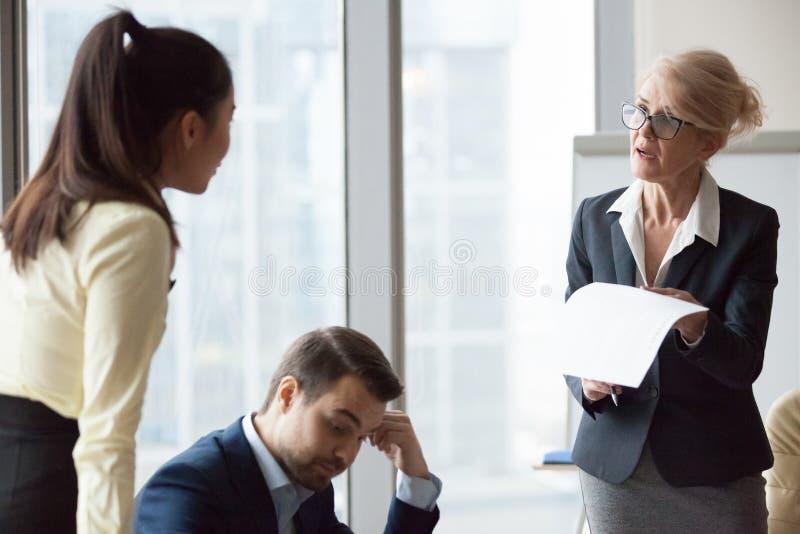 Verärgerte unbefriedigte DirektornGeschäftsfrau, die Arbeit kritisiert stockbild
