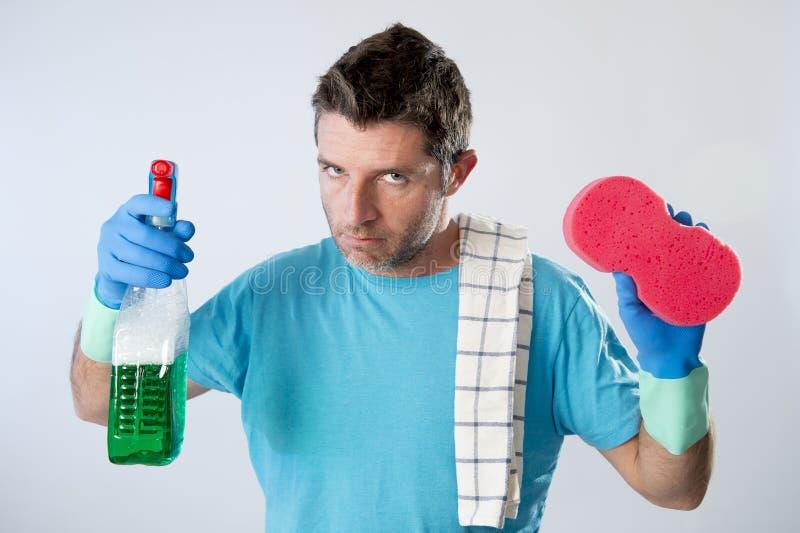Verärgerte und betonte Hausreinigung des Gesindedienstmannes oder des müden Ehemanns mit Sprühflasche und Schwamm lizenzfreies stockfoto
