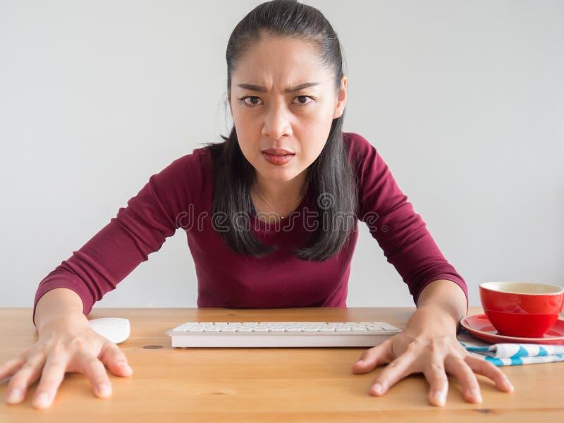 Verärgerte und gestörte Frau, die an ihrem Schreibtisch arbeitet lizenzfreies stockfoto