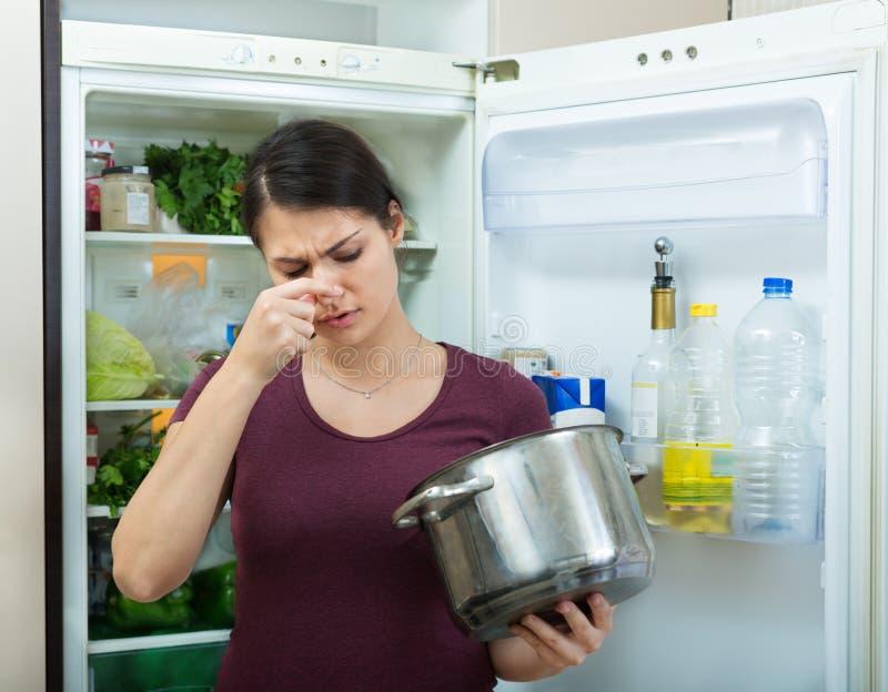 Verärgerte und umgekippte Hausfrau, die Topf mit widerlicher Mahlzeit untersucht lizenzfreie stockfotografie