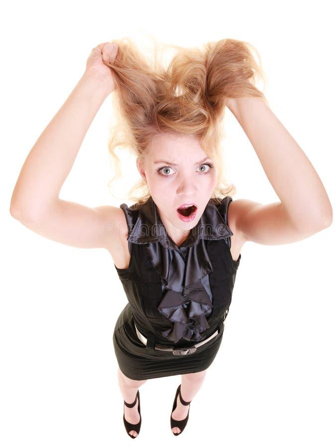 Verärgerte wütende Frau, die unordentliches Haar schreit und zieht stockfotografie