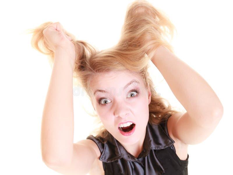 Verärgerte wütende Frau, die unordentliches Haar schreit und zieht stockbild