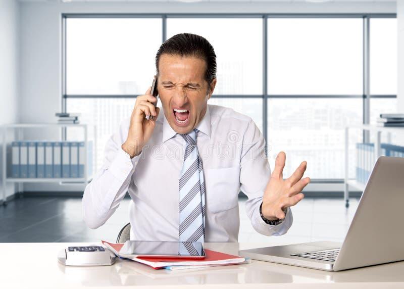 Verärgerter älterer Geschäftsmann im Druck, der an Handy am Computertisch arbeitet und spricht lizenzfreie stockfotos