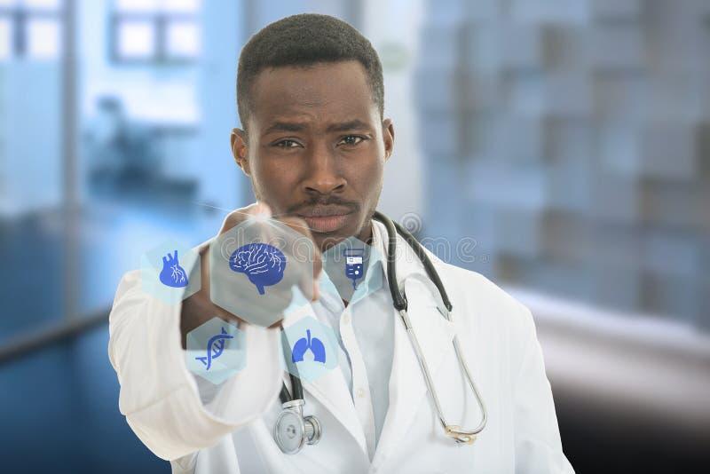 Verärgerter afrikanischer schwarzer männlicher Doktor, der Finger auf Sie mit Stethoskop um seinen Hals zeigt stockfotos