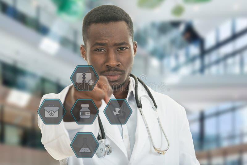 Verärgerter afrikanischer schwarzer männlicher Doktor, der Finger auf Sie mit Stethoskop um seinen Hals zeigt stockfotografie