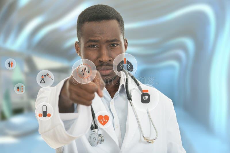 Verärgerter afrikanischer schwarzer männlicher Doktor, der Finger auf Sie mit Stethoskop um seinen Hals zeigt lizenzfreies stockfoto