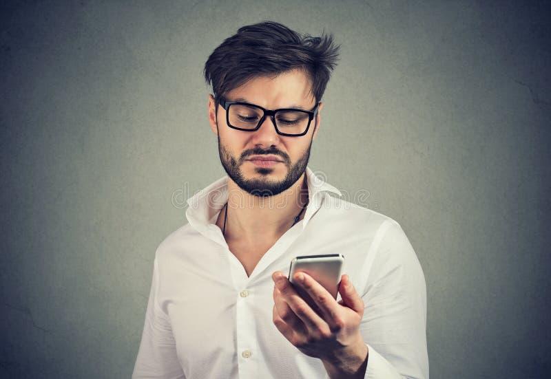 Verärgerter angewiderter Mann, der Smartphone verwendet stockfotografie