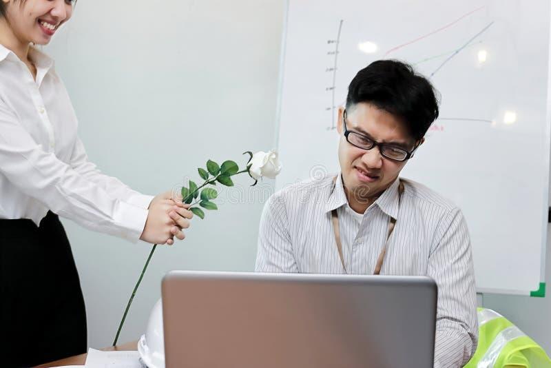 Verärgerter asiatischer Geschäftsmann lehnt weiße Rosen von der Schönheitsfrau ab stockfotos