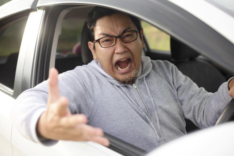 Verärgerter asiatischer männlicher Fahrer, schreiendes Zeigen von seinem Auto lizenzfreie stockfotos