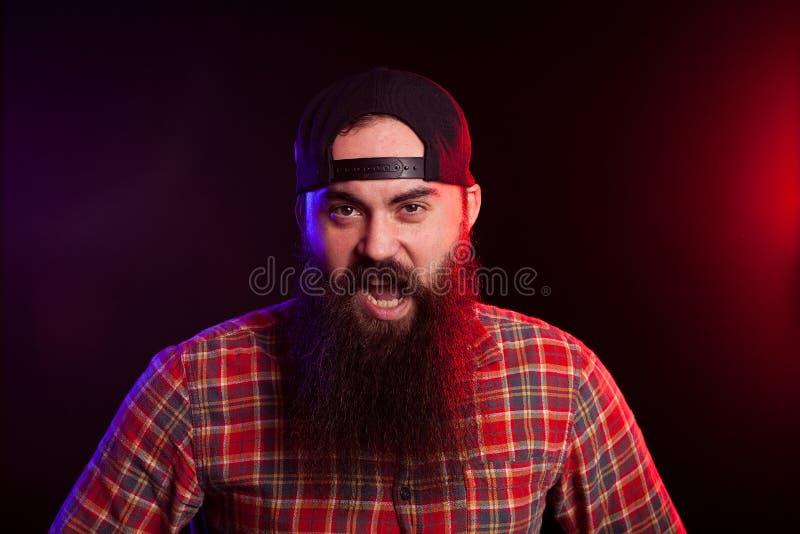 Verärgerter ausdrucksvoller bärtiger Hippie-Mann auf schwarzem Hintergrund stockbilder