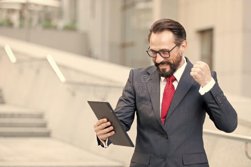 Verärgerter bärtiger Geschäftsmann kleidete in der blauen Klage an, die mit der Faust tablet während Büros der Videokonferenz des lizenzfreie stockfotos